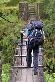 Trekker passing on a suspension bridge in the Himalayas — Stock Photo
