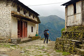 Trekker with backpack in a mountain village — Stock Photo