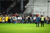 Football hooligans run on the soccer field — Stock Photo