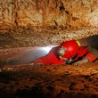 Narrow cave passage with a cave explorer — Stock Photo #43809039