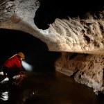 Постер, плакат: Cave explorer speleologist exploring the underground