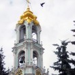 Bell tower, green trees, bird flying high in Trinity Sergius Lavra — Stock Photo