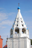Old white bell tower with many archs, blue cupola and golden cross on the top — Stock Photo