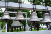 Many bells. Green trees background. — Stock Photo