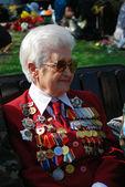 Una mujer de veterano de guerra posee flores. — Foto de Stock