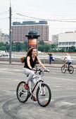 A young woman rides a bike — ストック写真