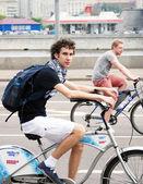 Un jeune homme monte un vélo et un coup d'oeil à la caméra — Photo