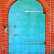 ������, ������: Green metallic door on red bricks wall