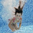 Stock Photo: Underwater child jumps to swimming pool