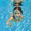Happy smiling underwater child in swimming pool — Stock Photo #14006126
