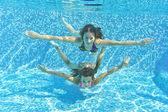 Usmívající se rodina pod vodou v bazénu — Stock fotografie