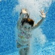 Happy smiling underwater child in swimming pool — Stock Photo #14130714