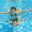 Happy smiling family underwater in swimming pool — Foto Stock