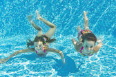 Happy smiling underwater children in swimming pool — Stock Photo