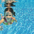 Happy smiling underwater child in swimming pool — Stock Photo #14287639