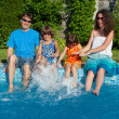 Family having fun near swimming pool - Stock Photo