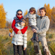 Happy family of four in autumn park — Stock Photo