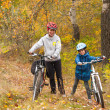 Happy family on bikes in autumn forest — Stock Photo #14534417