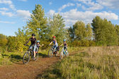 Active family on bikes cycling outdoors — Stock Photo