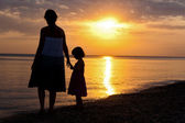 Family silhouettes on sunset beach — Stockfoto