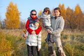 счастливая семья из четырех человек в осенний парк — Стоковое фото