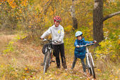Happy family on bikes in autumn forest — Stock Photo
