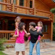 Happy smiling family near wooden house — Stock Photo #16195449