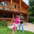 Happy smiling family near wooden house — Stock Photo #16195525