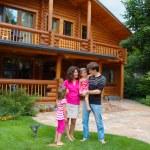 sorridente e feliz família perto da casa de madeira — Foto Stock