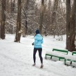 Active happy woman runner jogging outdoors in snowy park in winter — Stock Photo