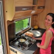 Woman cooking in camper - Stock Photo