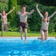 Happy family with kids jumping to swimming pool — ストック写真