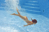 Little girl swims underwater in pool — Stock Photo