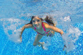 Happy active child swims underwater in pool — Stock Photo