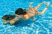 Děti plavat pod vodou v bazénu — Stock fotografie