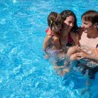 Happy family having fun in swimming pool — Stock Photo