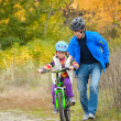 Stock Photo: Father teaching child to ride bike