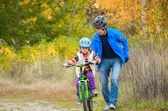 Father teaching child to ride bike — Stock Photo