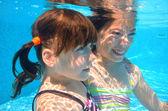Happy girls swim underwater in pool — Stock Photo