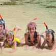 Happy family in snorkels on tropical beach — Stock Photo