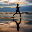 Silhouette of woman jogger running on sunset beach with reflection — Stock Photo #49364333