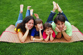 Family with two kids on grass — Foto Stock