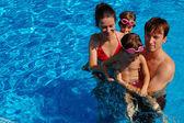 Happy family having fun in swimming pool — Stock Photo