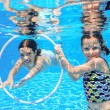 Happy active kids play underwater in swimming pool — Stock Photo #50136933