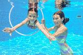 Happy active kids play underwater in swimming pool — Stock Photo