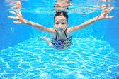 Happy active underwater child swims in pool — Stock Photo