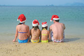 Family in santa hats having fun on beach — Stock Photo