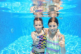 Happy active kids swim in pool and play underwater — Stock Photo