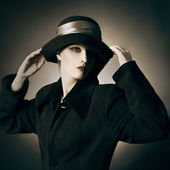 Elegant retro woman in black coat and hat — Stock Photo