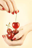 Hands cherry with red nails manicure — Stock Photo